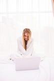 Donna che si trova sul letto sotto il copriletto e che per mezzo del computer portatile Fotografie Stock