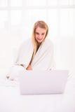 Donna che si trova sul letto sotto il copriletto e che per mezzo del computer portatile Immagini Stock Libere da Diritti