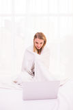 Donna che si trova sul letto sotto il copriletto e che per mezzo del computer portatile Immagini Stock