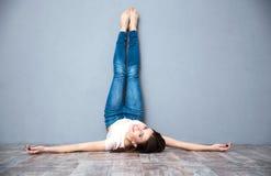 Donna che si trova sul pavimento con le gambe sollevate su Fotografie Stock Libere da Diritti