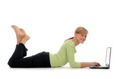 Donna che si trova sul pavimento per mezzo del computer portatile Fotografia Stock
