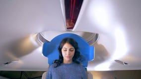 Donna che si trova sull'analizzatore di RMI o di CT durante l'esame medico archivi video