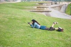 Donna che si trova sull'erba che prende un'immagine Fotografia Stock Libera da Diritti