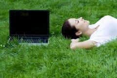 Donna che si trova sull'erba con il computer portatile Immagine Stock