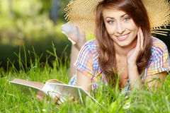Donna che si trova sull'erba con libri Immagini Stock