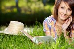 Donna che si trova sull'erba con libri Fotografia Stock