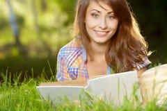 Donna che si trova sull'erba con libri Fotografia Stock Libera da Diritti