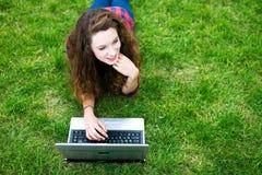 Donna che si trova sull'erba per mezzo del computer portatile Fotografia Stock Libera da Diritti