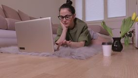 Donna che si trova sulla coperta e che per mezzo del computer portatile archivi video