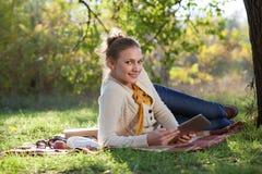 Donna che si trova sulla lettiera su erba verde con ipad fotografia stock libera da diritti