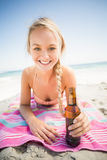 Donna che si trova sulla spiaggia con la bottiglia di birra Fotografia Stock Libera da Diritti