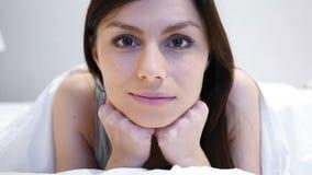 Donna che si trova sullo stomaco a letto che esamina macchina fotografica, fine su archivi video
