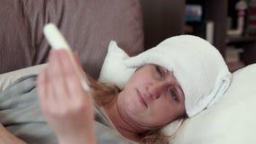 Donna che si trova sullo strato Ha il raffreddore, un'emicrania video d archivio