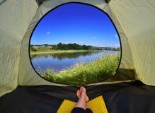 Donna che si trova in tenda con una vista della montagna e del cielo Immagini Stock Libere da Diritti