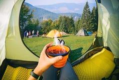 Donna che si trova in una tenda con caffè, vista di campeggio fotografia stock libera da diritti