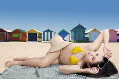 Donna che si trova vicino alle capanne della spiaggia Immagine Stock