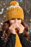 Donna che soffia il suo naso nel tessuto, ritratto all'aperto di inverno Immagine Stock