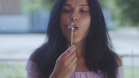 Donna che soffia su un dente di leone al rallentatore video d archivio