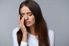 Donna che soffre dal forte dolore, avendo emicrania, fronte commovente Immagini Stock Libere da Diritti