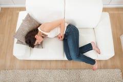 Donna che soffre dal mal di stomaco sul sofà fotografie stock