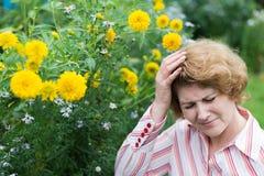 Donna che soffre dall'emicrania allergica ai fiori Fotografie Stock
