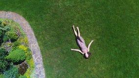 Donna che sogna menzogne sull'erba, vista aerea, mosca girante del fuco sopra signora del giardino stock footage