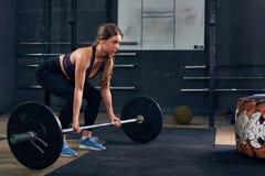 Donna che solleva bilanciere pesante nella palestra di CrossFit Fotografia Stock