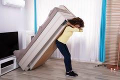Donna che solleva Sofa In Living Room immagini stock