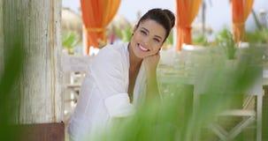 Donna che sorride all'aperto al ristorante della spiaggia stock footage