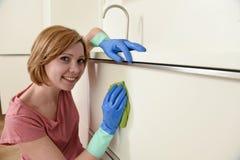 Donna che sorride lavaggio e pulizia felici e positivi con il panno una cucina moderna Fotografia Stock