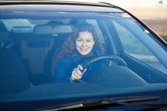 Donna che sorride tramite il parabrezza dell'automobile fotografie stock