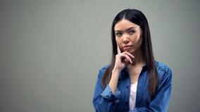 Donna che sospetta qualcosa, pensando al piano abile su fondo grigio fotografia stock libera da diritti