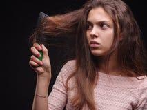 Donna che spazzola capelli aggrovigliati con un pettine su un fondo nero Ragazza che esamina capelli malati nocivi Concetto di pr fotografia stock libera da diritti