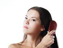 Donna che spazzola i suoi capelli Immagini Stock Libere da Diritti