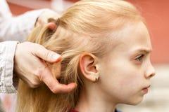 Donna che spazzola i suoi capelli della figlia fotografia stock