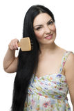 Donna che spazzola i suoi capelli neri lunghi Fotografia Stock Libera da Diritti