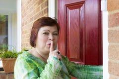 Donna che spia vicino alla porta del vicino Fotografia Stock Libera da Diritti