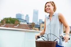 Donna che spinge bici con l'orizzonte della città nel fondo Immagine Stock Libera da Diritti