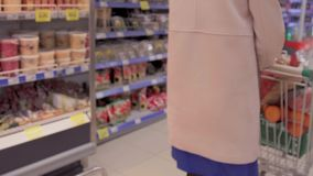 Donna che spinge carrello in drogheria stock footage