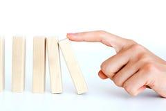 Donna che spinge un blocco di legno per iniziare un effetto di domino Fotografia Stock
