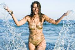 Donna che spruzza acqua alla spiaggia Fotografia Stock