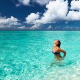 Donna che spruzza acqua con i capelli nell'oceano Fotografia Stock