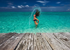 Donna che spruzza acqua con i capelli nell'oceano Immagini Stock