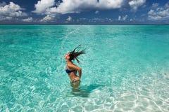 Donna che spruzza acqua con i capelli nell'oceano Immagine Stock Libera da Diritti