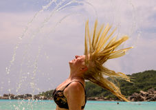 Donna che spruzza acqua con i suoi capelli Immagini Stock