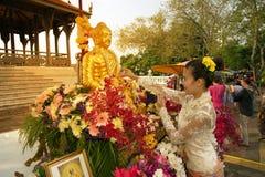 Donna che spruzza acqua profumata sull'immagine di Buddha nel festival di Songkran Fotografia Stock Libera da Diritti