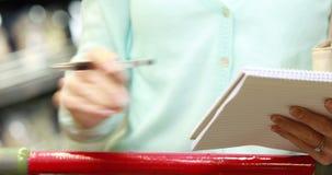 Donna che spunta la lista della drogheria stock footage