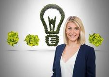 Donna che sta accanto alla lampadina della natura verde con le palle di carta sgualcite Immagine Stock