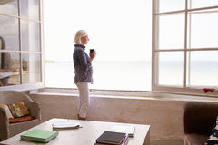 Donna che sta alla finestra e che esamina bella vista della spiaggia immagine stock