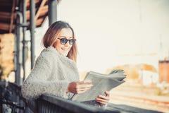 Donna che sta alla stazione ferroviaria e che legge i giornali Immagini Stock